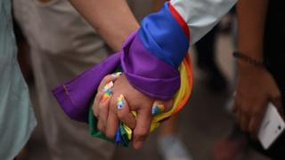 A couple holds hands wrapped in a rainbow flag